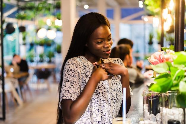 Wesoła afroamerykanin młoda kobieta w letniej sukience w kawiarni wącha białe kwiaty w wazonie.