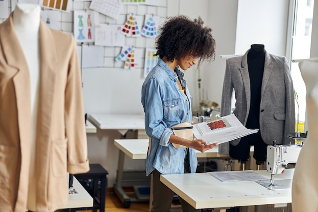 Wesoła afroamerykanka patrzy na nowe rysunki przy stole z maszyną do szycia