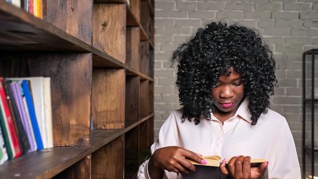 Wesoła afroamerykanka w stylowej bluzce bierze książkę z drewnianej półki, aby przygotować się do testu we współczesnej bibliotece z bliska