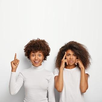 Wesoła afroamerykanka wskazuje nad palcem wskazującym, jej intensywna przyjaciółka dotyka skroni, próbuje przypomnieć sobie ważne informacje