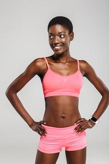 Wesoła afroamerykańska sportsmenka pozuje i uśmiecha się na białym tle nad białą ścianą