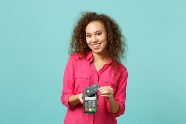 Wesoła afrykańska dziewczyna trzymaj bezprzewodowy nowoczesny bankowy terminal płatniczy do przetwarzania, nabywania płatności kartą kredytową na białym tle na niebieskim tle turkusu. ludzie emocje, koncepcja stylu życia. makieta miejsca na kopię.