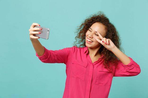 Wesoła afrykańska dziewczyna w zwykłych ubraniach pokazując znak zwycięstwa, robi selfie strzał na telefon komórkowy na białym tle na niebieskim tle turkusu. ludzie szczere emocje, koncepcja stylu życia. makieta miejsca na kopię.