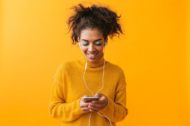 Wesoła afrykańska kobieta ubrana w sweter stojący na białym tle, słuchanie muzyki przez słuchawki, trzymając telefon komórkowy