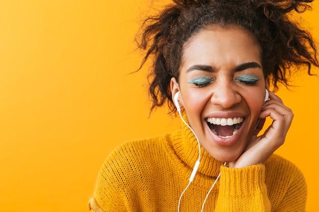 Wesoła afrykańska kobieta ubrana w sweter stojący na białym tle, słuchanie muzyki przez słuchawki
