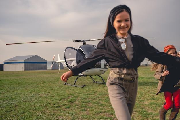 Wesoła animowana dziewczyna biegająca na tle helikoptera na lotnisku