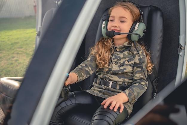 Wesoła animowana dziewczyna w zestawie słuchawkowym, siedząca na fotelu pilota w helikopterze