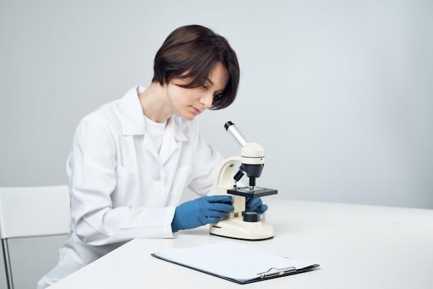 Wesoła asystentka w laboratorium w białym fartuchu, profesjonalne eksperymenty naukowe