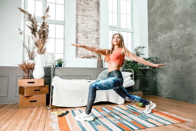 Wesoła atletka o blond włosach rzuca się do sypialni podczas treningu online