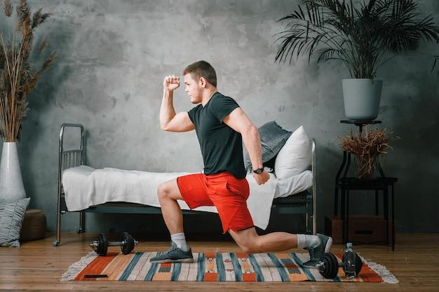 Wesoła atletka o czarnych włosach rzuca się do sypialni obok laptopa z treningiem online. młody człowiek uprawia sport w domu.