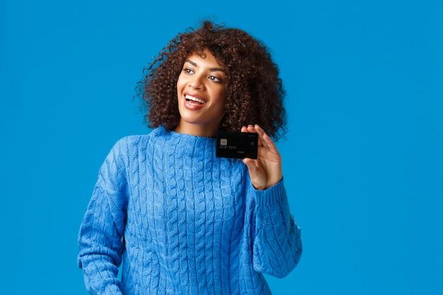 Wesoła atrakcyjna afroamerykańska kobieta z afro fryzurą, zimowy sweter