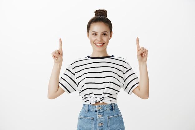 Wesoła atrakcyjna brunetka szeroko uśmiechnięta, wskazująca palcami w górę