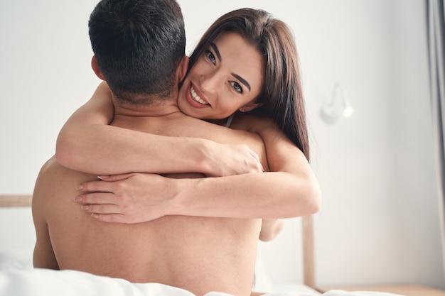 Wesoła atrakcyjna dama z ramionami wokół szyi męża patrząca przed nią