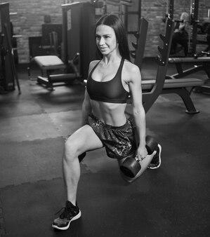 Wesoła atrakcyjna dziewczyna robi ćwiczenia rzuca się z hantlami w ręce na siłowni