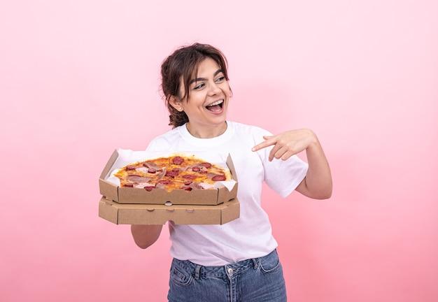 Wesoła atrakcyjna dziewczyna z pizzą w pudełku na różowym tle