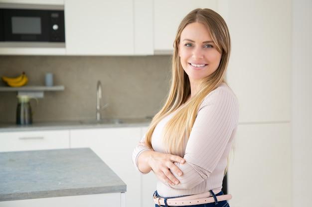 Wesoła atrakcyjna jasnowłosa młoda kobieta pozuje z rękoma w kuchni