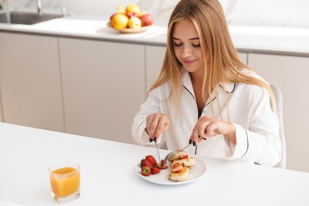 Wesoła atrakcyjna kobieta w piżamie jedząca śniadanie i uśmiechająca się siedząc przy stole w jasnej kuchni
