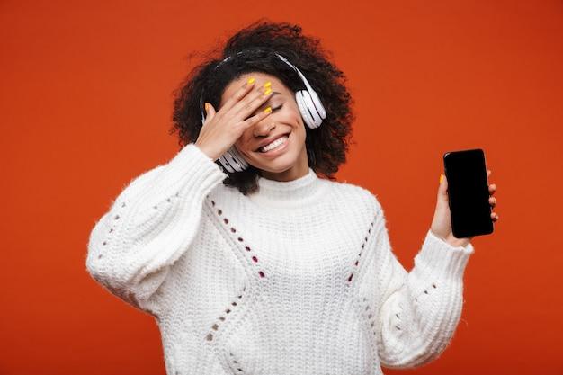 Wesoła, atrakcyjna młoda afrykańska kobieta w bezprzewodowych słuchawkach, stojąca na białym tle nad czerwoną ścianą, pokazująca pusty ekran telefonu komórkowego