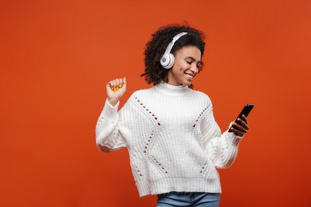 Wesoła, atrakcyjna młoda afrykańska kobieta w bezprzewodowych słuchawkach, stojąca na białym tle nad czerwoną ścianą, trzymająca telefon komórkowy, tańcząca