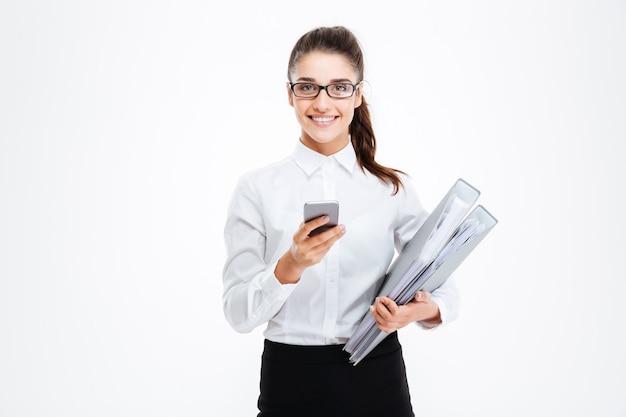Wesoła atrakcyjna młoda bizneswoman w okularach trzymająca foldery i używająca telefonu komórkowego nad białą ścianą
