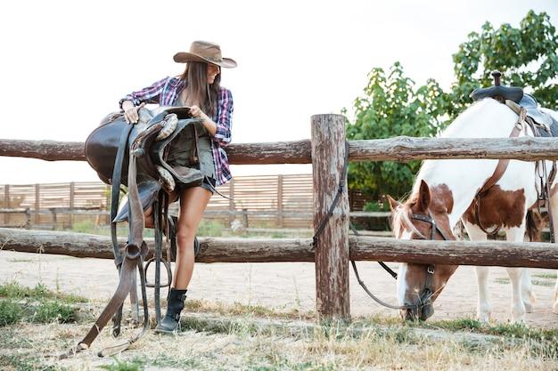Wesoła atrakcyjna młoda kobieta cowgirl w kapeluszu trzymająca siodło do jazdy konnej