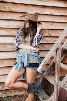 Wesoła atrakcyjna młoda kobieta kowbojka stojąca i uśmiechająca się w pobliżu domu