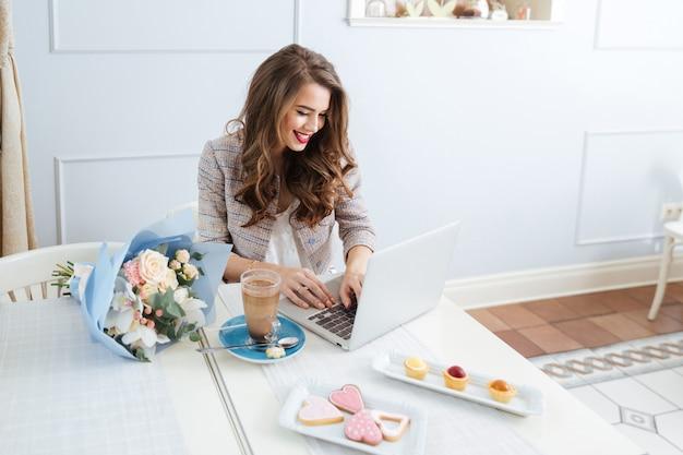 Wesoła atrakcyjna młoda kobieta pije latte i korzysta z laptopa w kawiarni
