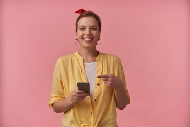 Wesoła atrakcyjna młoda kobieta w żółtej koszuli z pałąkiem na głowie za pomocą telefonu komórkowego i wskazując na smartfonie na różowej ścianie