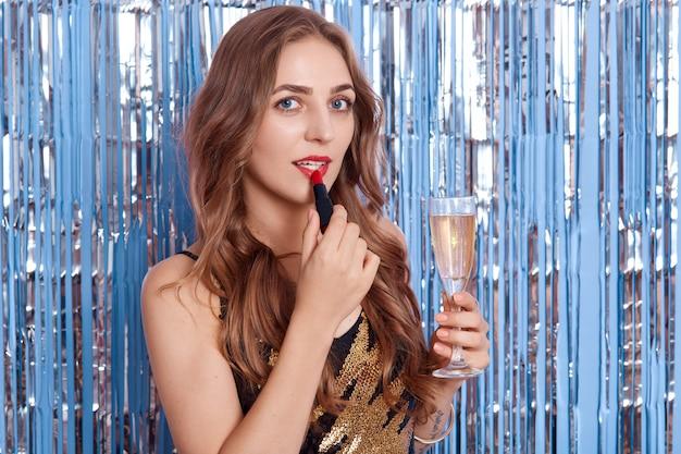 Wesoła atrakcyjna młoda kobieta z jasnym makijażem, trzymając kieliszek wina lub szampana, pani stosuje pomadę