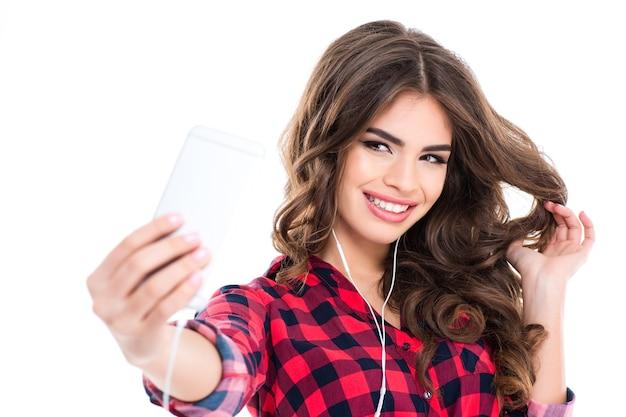 Wesoła atrakcyjna młoda kobieta z pięknymi długimi włosami uśmiecha się i robi selfie na białej ścianie