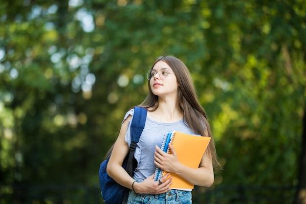 Wesoła atrakcyjna młoda kobieta z plecakiem i notebookami, stojąc i uśmiechając się w parku