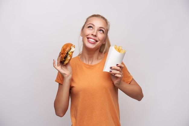 Wesoła atrakcyjna młoda niebieskooka blondynka trzyma burgera i frytki w uniesionych dłoniach i patrzy radośnie w górę, uśmiechając się szeroko, pozując na białym tle