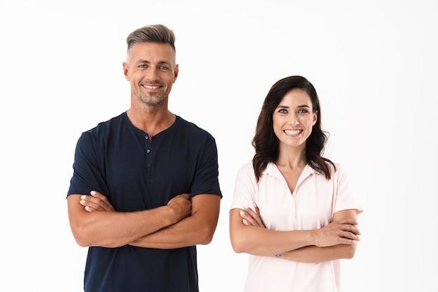 Wesoła atrakcyjna para ubrana w swobodny strój, stojąca na białym tle nad białą ścianą, z założonymi rękoma
