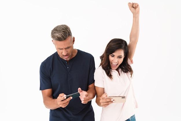 Wesoła atrakcyjna para w swobodnym stroju, stojąca na białym tle nad białą ścianą, grająca w gry na telefonach komórkowych, świętująca sukces