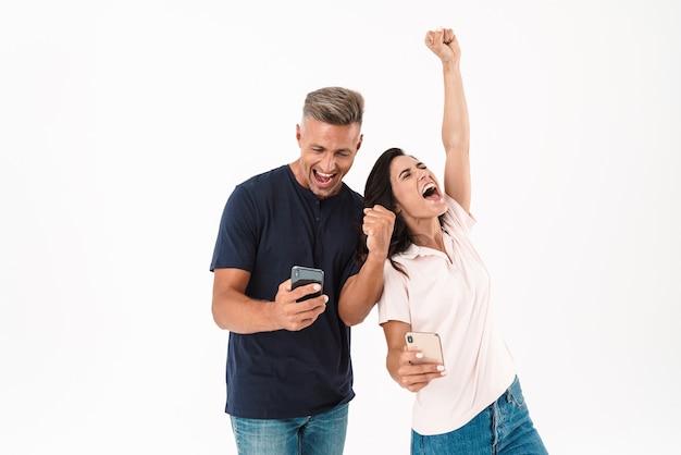 Wesoła atrakcyjna para w swobodnym stroju, stojąca na białym tle nad białą ścianą, korzystająca z telefonu komórkowego, świętująca sukces