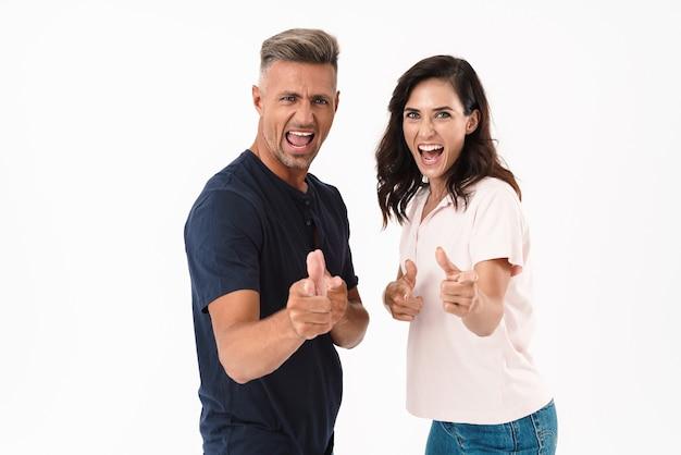 Wesoła, atrakcyjna para w swobodnym stroju, stojąca na białym tle nad białą ścianą, pokazując kciuk do góry