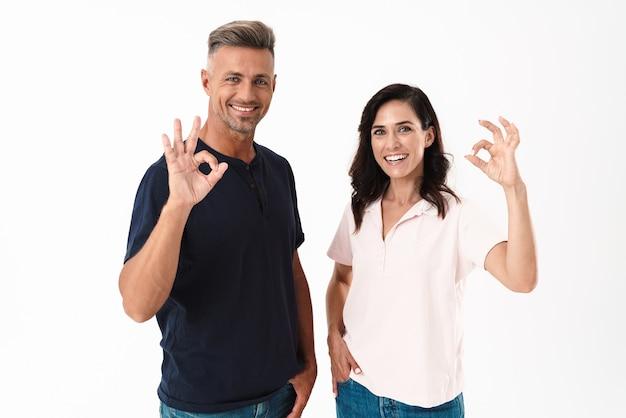 Wesoła, atrakcyjna para w swobodnym stroju, stojąca na białym tle nad białą ścianą, pokazująca ok