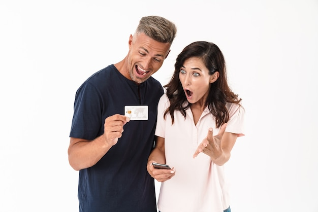 Wesoła atrakcyjna para w swobodnym stroju stojąca na białym tle nad białą ścianą, robiąca zakupy online za pomocą telefonu komórkowego i karty kredytowej