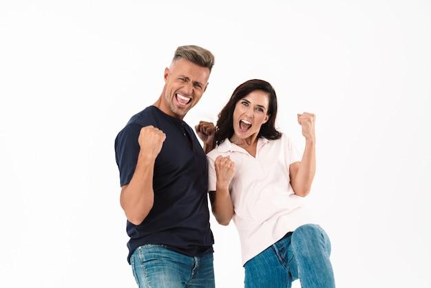 Wesoła, atrakcyjna para w swobodnym stroju, stojąca na białym tle nad białą ścianą, świętująca sukces