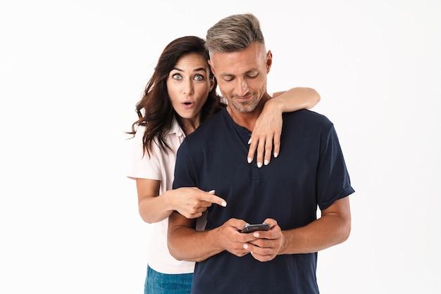 Wesoła atrakcyjna para w swobodnym stroju, stojąca na białym tle nad białą ścianą, wskazująca palcem na telefon komórkowy