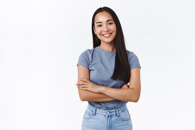 Wesoła azjatycka brunetka w koszulce, skrzyżowane ręce nad klatką piersiową w swobodnej pozie, pochylona głowa i uśmiechnięta, mająca przyjemną rozmowę, wyrażająca pozytywność i zdecydowaną postawę, biała ściana