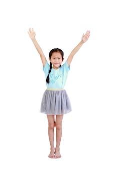 Wesoła azjatycka dziewczynka z warkoczykiem stojąc i podnosić ręce na białym tle na białej ścianie