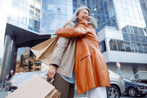Wesoła azjatycka kobieta przytula dojrzałą damę z licznymi torbami na zakupy na ulicy miasta