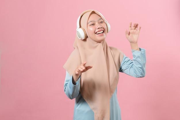 Wesoła azjatycka muzułmańska dziewczyna słuchająca muzyki w bezprzewodowych słuchawkach i tańcząca na różowym tle