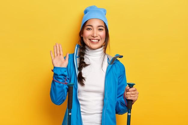Wesoła azjatycka podróżniczka trzyma sprzęt turystyczny, faluje palmę, wita przyjaciela w górach, jest aktywnym turystą, przyjemnie się uśmiecha, odizolowana na żółtej ścianie