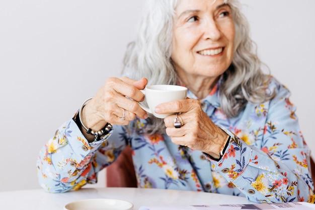 Wesoła babcia popijająca kawę w kawiarni