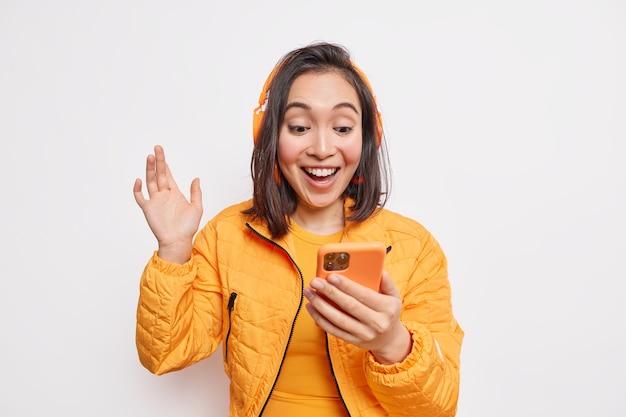 Wesoła beztroska azjatycka nastolatka trzyma fale smartfona ręka sprawia, że rozmowa wideo wybiera piosenkę na internetowej platformie muzycznej słucha ulubionego podcastu używa bezprzewodowych słuchawek ubrana w pomarańczową kurtkę