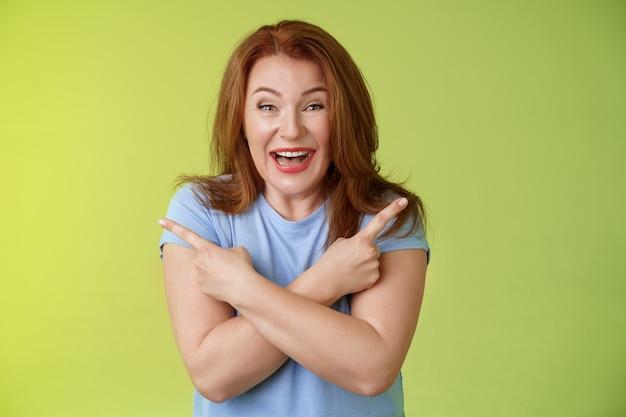 Wesoła beztroska entuzjastyczna ruda zabawna dojrzała kobieta dobrze się bawiąca pozytywna postawa skrzyżowane ramiona ciało skierowane w bok pokaż lewy prawy produkty śmiejące się radośnie jak obie opcje zielona ściana