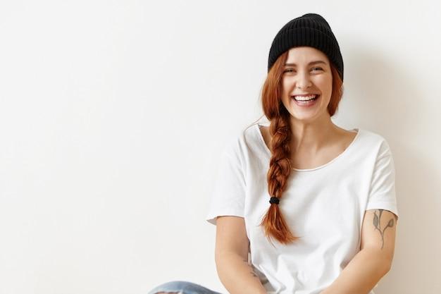 Wesoła beztroska ładna hipster dziewczyna z tatuażem siedzi na podłodze na białej ścianie