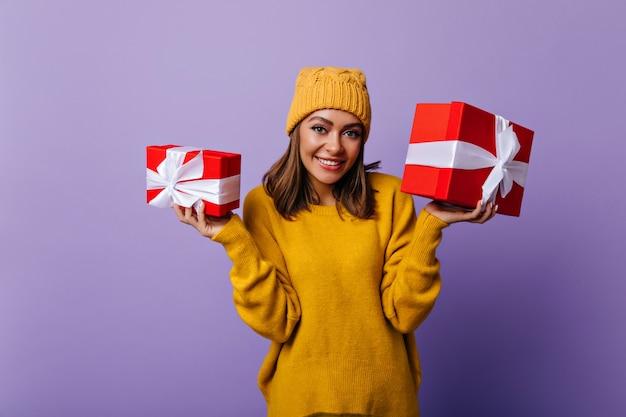 Wesoła biała dziewczyna w stylowym stroju przygotowuje prezenty na nowy rok dla rodziny. kryty portret uśmiechnięta piękna kobieta z prezentami.